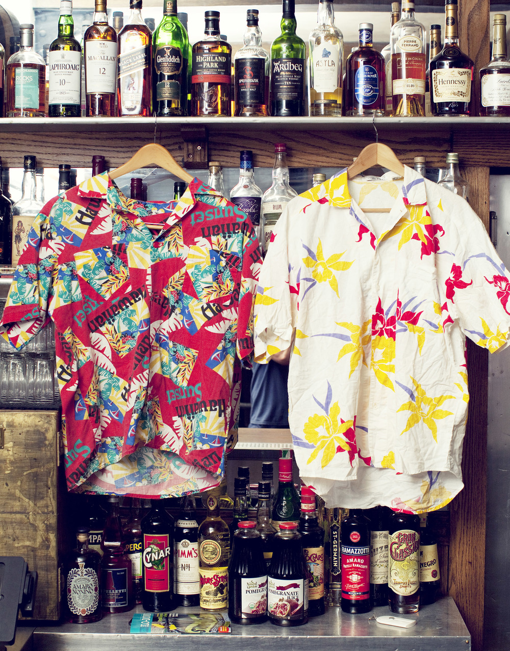 Top:  Elvis'  Blue Hawaii  album cover, Tom Selleck as Magnum, P.I..  Bottom:  Shirts found in Los Angeles (on the left, the first Clay ever purchased) hang at the Black Crescent bar in New York City.
