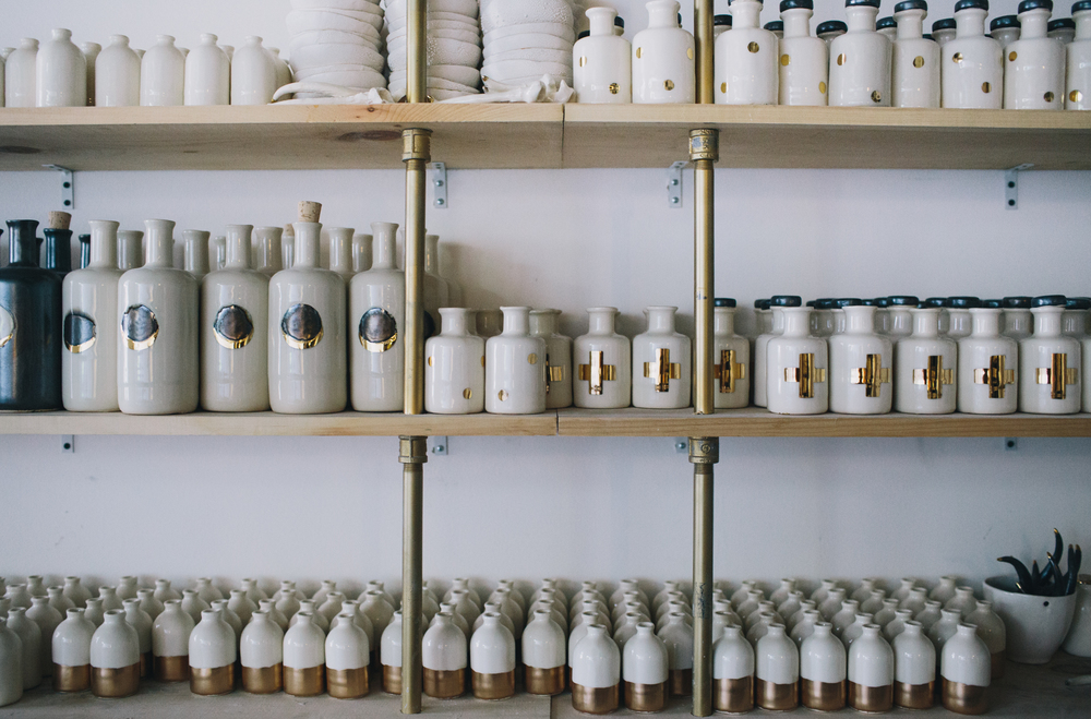 Handmade porcelain bud vases and apothecary jars line the shelves in Courtney's workspace.