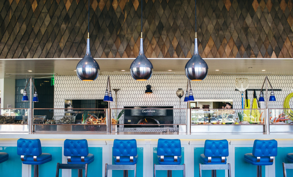 A large oyster bar on the top floor surrounds a wood oven, prepped to roast fish and shellfish.