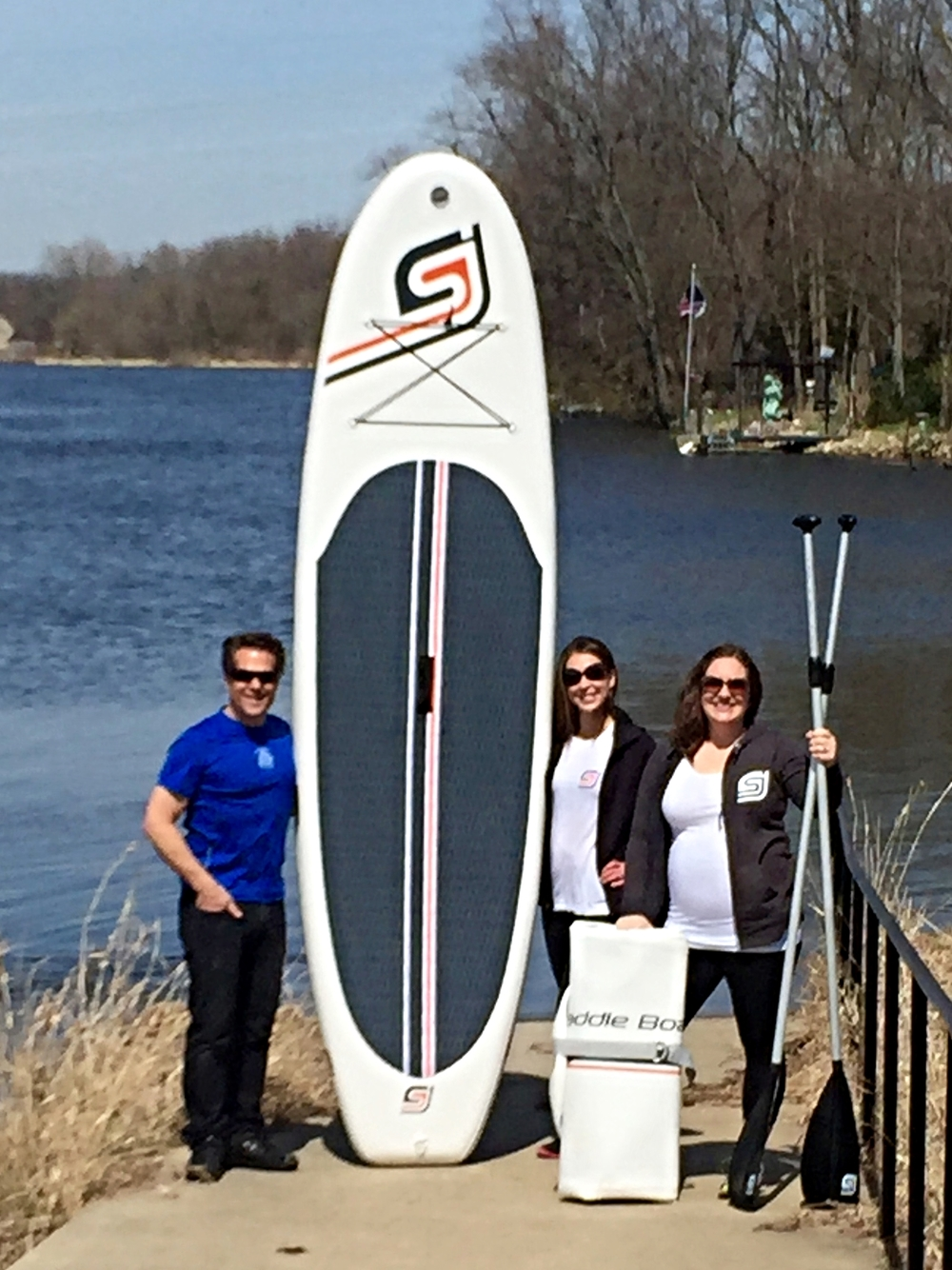 Bruce Heidlauf (from left), Bridgett Syzdek and Sarah Traven stand with a paddle board. Traven started a new business, SJ Paddle Boards, selling the boards. Heidlauf, who owns Mill Race Cyclery in Geneva, will begin offering Traven's paddle boards for sale or rent Memorial Day weekend. In addition, Syzdek will teach a yoga class to people who are standing on the paddle boards July 4 at Island Park in Geneva.