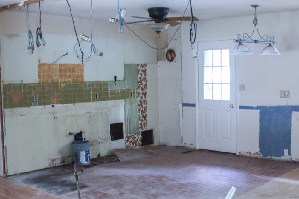 Here is a picture of what the kitchen looked like after we had taken out all the cabinets, removed a wall (hence the hanging electrical), taken out the backsplash, and ripped up all the flooring.