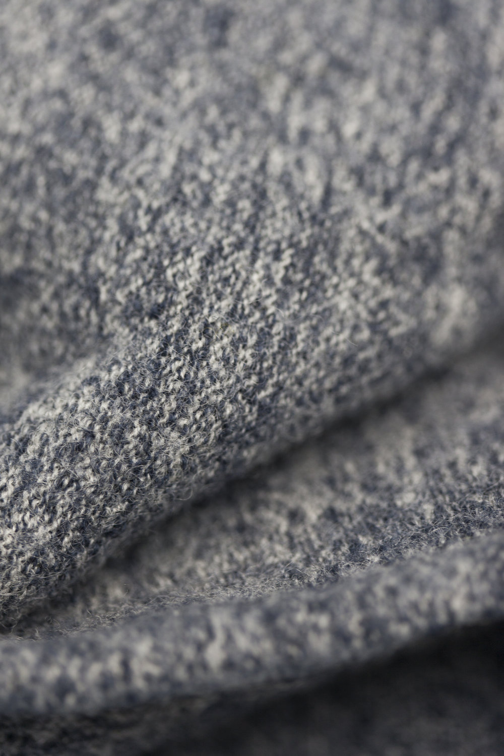 100% wool which has been through several different processes. After finishing the knitting process the yarns are boiled under very controlled conditions. The boiling creates this really fine compact texture which is still soft and contains all the benefits from the wool. Used on style Melange Boiled Cardigan.