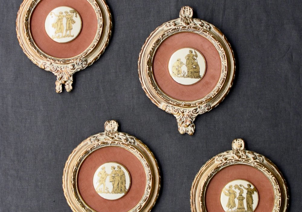 Probably brought back as a souvenir from Greece, these gold gilt Grecian figures on white porcelain disks are displayed on a salmon colored velvet in gold frames. They caught my attention.