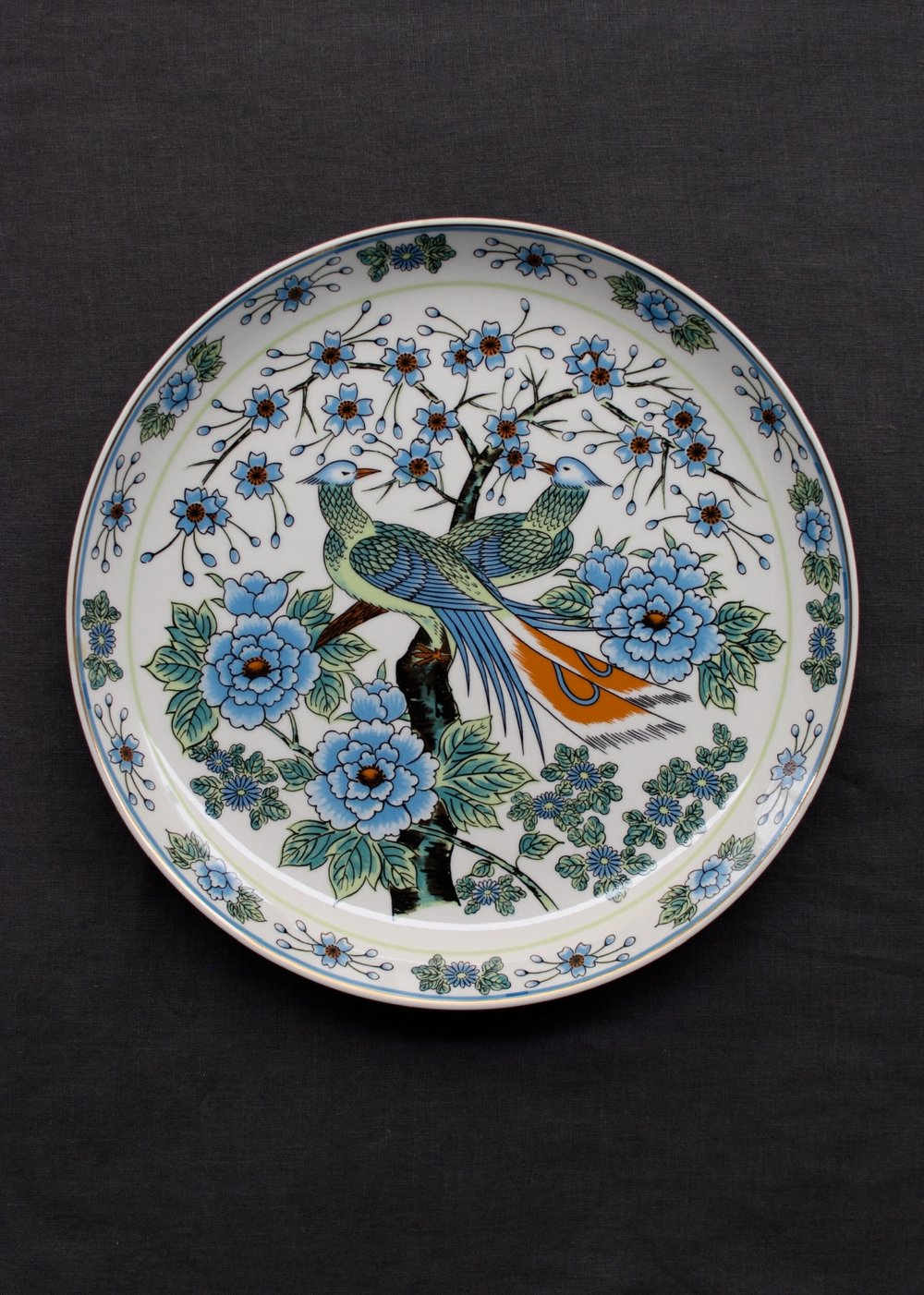 Beautiful decorative charger with bird and floral motifs.