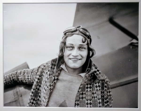 """Stunt pilot Dorothy Hester was probably around age nineteen when she posed next to a plan for this photograph. Hester, from Milwaukie, Oregon, learned to fly at the Rankin School of Flying in Portland. She impressed Tex Rankin, and he taught her aerobatics. In June 1930, at age nineteen, she became the first woman to perform a stunt called an outside loop. Hester wowed audiences both in Oregon and at air shows around the nation, set world records for stunt flying, and opened her own flight school. She left her career in aviation after marrying in 1934."""