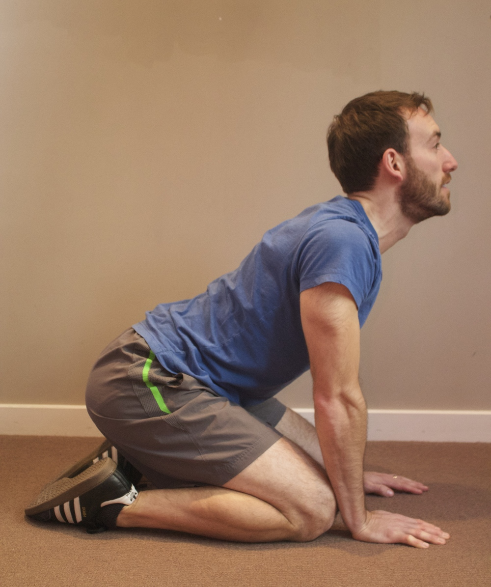 Exhale, arch mid-back, and tilt chin upward.