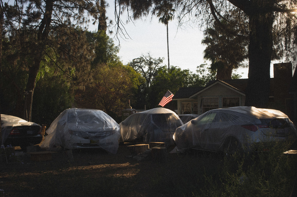 Cars wrapped in plastic covers in the  front of a suburbs house in North Hills, CA - 2014
