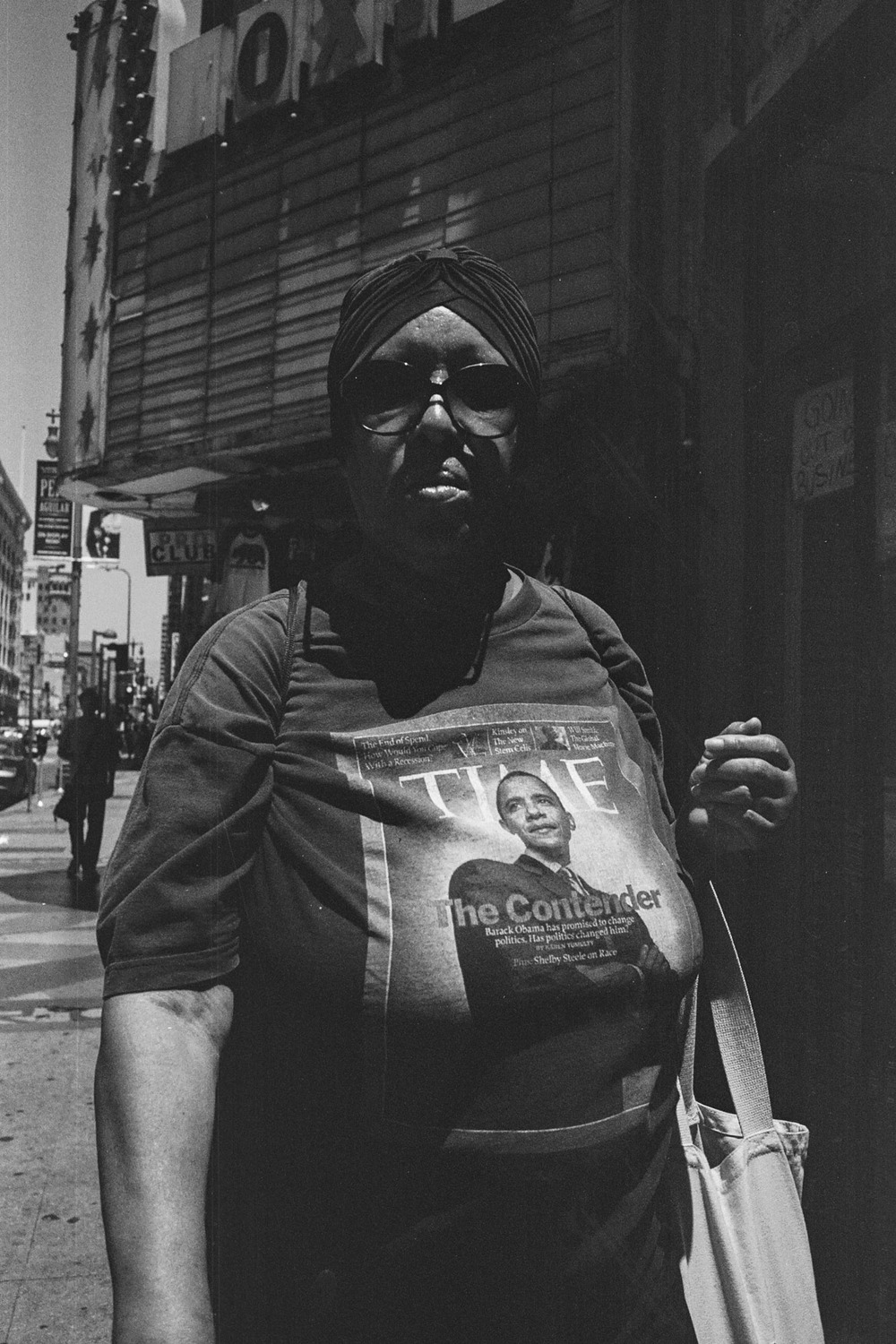 Woman wearing shirt with Time Magazine cover of President Obama walking on the streets of Downtown LA, CA - 2014