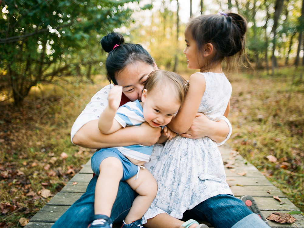 Mom snuggles her children during Ventura CA family photography session