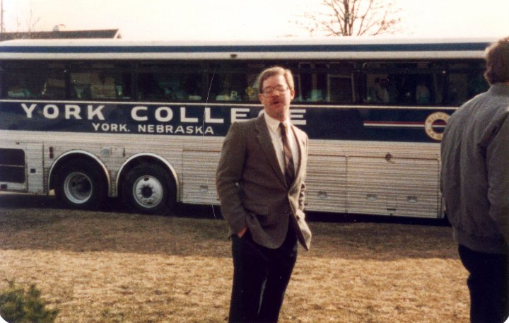 A young Dr. Roush waits by a York College bus.
