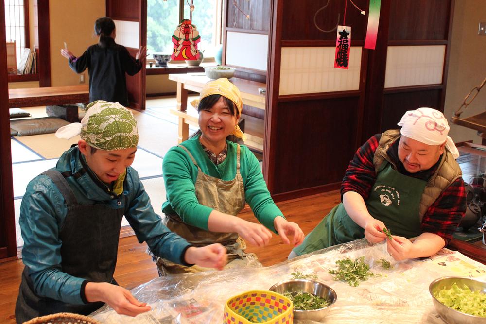 """【里山ごはん食べに行こう】    のどかな里山景色の中で""""手作り""""にこだわりながら、季節に合わせたお惣菜や郷土料理を教わる里山料理教室です。地元のお母さん達に教わりながらみんなで作ってワイワイ試食。野菜の処理の仕方、混ぜ合わせ方、練り方、調味料の加減などなど直接見ながら、聞きながらだから失敗無しです(笑)春はふきのとうでばっけ味噌作り、初夏の笹巻、梅干し作り、秋は栗の手ほどき、そして新米。冬の保存食作りなど季節に応じた暮らしの知恵やレシピがたくさん登場します。"""