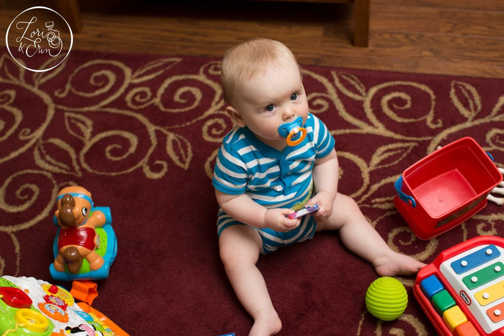 This image shows Lucas surrounded by his toys, but he is less interested in looking up at the camera, he looks small in the space and it is not nearly as engaging as the first image.
