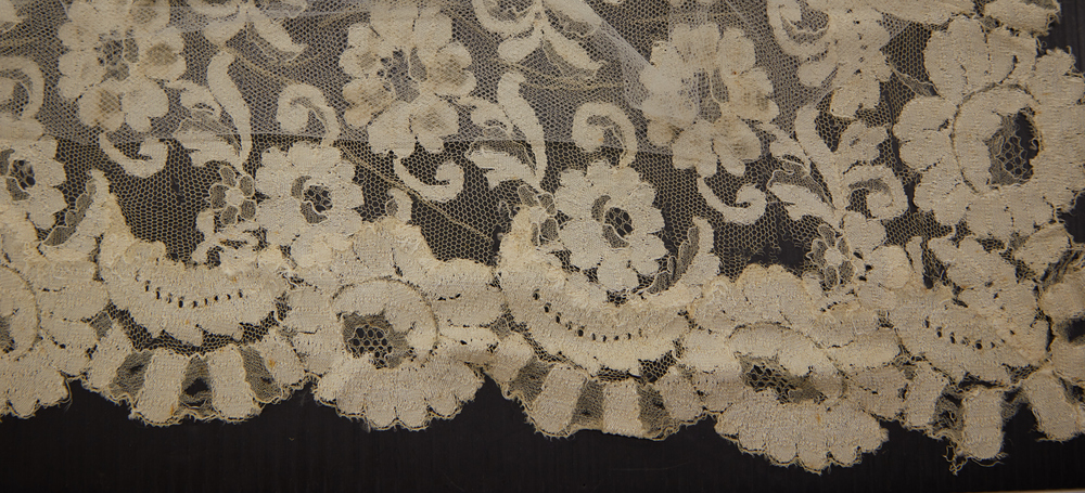 During treatment as the conservator removes original lace panel from silk netting.