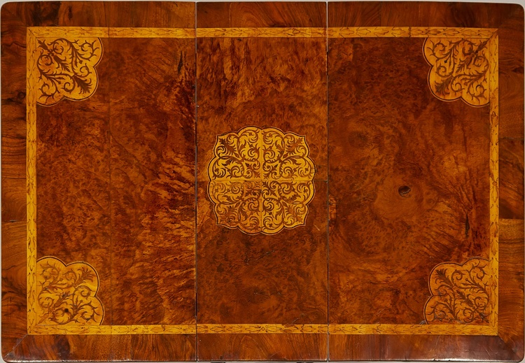 Thin, carefully cut pieces of wood veneer were pieced together to create the delicate design of this marquetry table top. Click    here        to learn more about the treatment of this table.