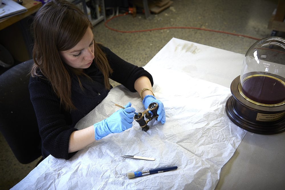 Senior Objects Conservator, Sian Pirnie, treating the opera glasses.