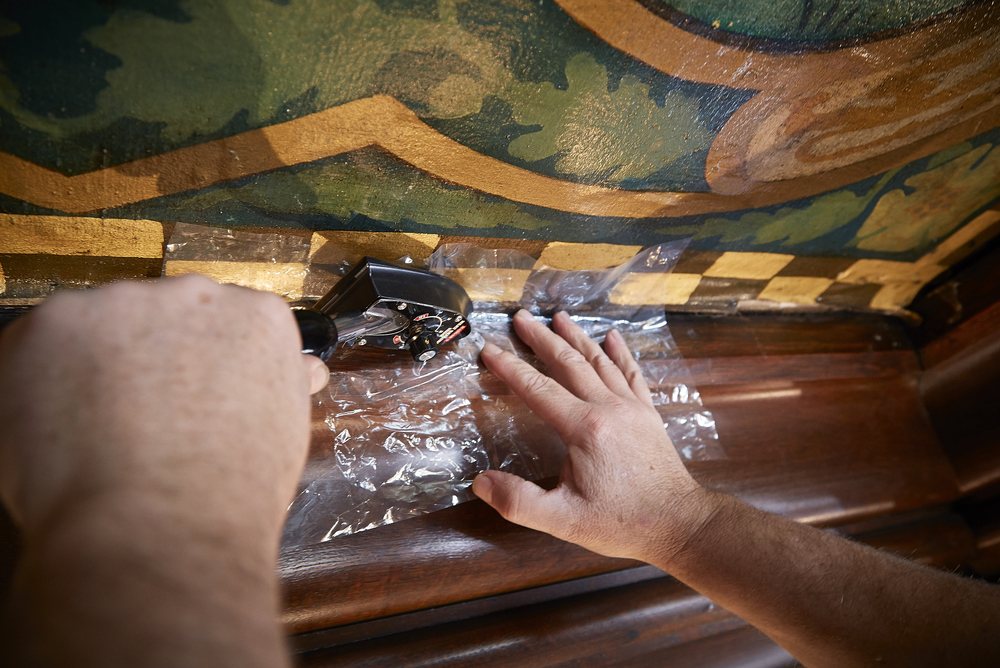 Conservator Stephen Ryan, working on one of the panels to flatten out any ripples that have occurred over time, using conservation techniques.