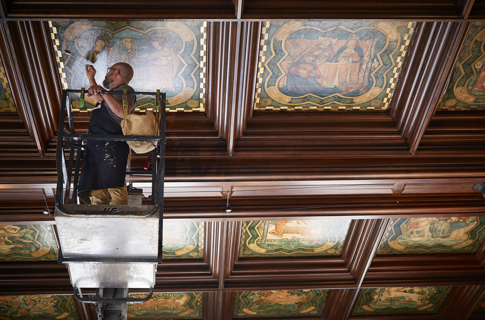 Conservator Andrew Rigby working on one of the ceiling panels in the Michigan Room.