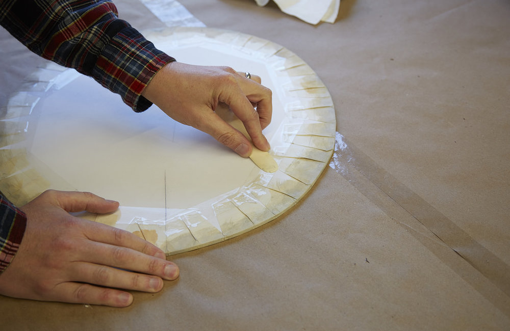 A new drum head is being created in preparation for exhibition.