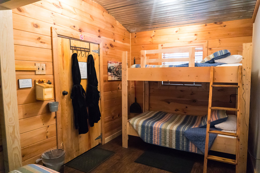 Mountain Laurel - Previously: Cabin 2B. Sleeps 2-4. Perfect for couples, families, or friends. Mountain Laurel comes equipped with one queen bed and one bunk bed with top and bottom twin mattress. This cabin faces the babbling brook flowing through the property.