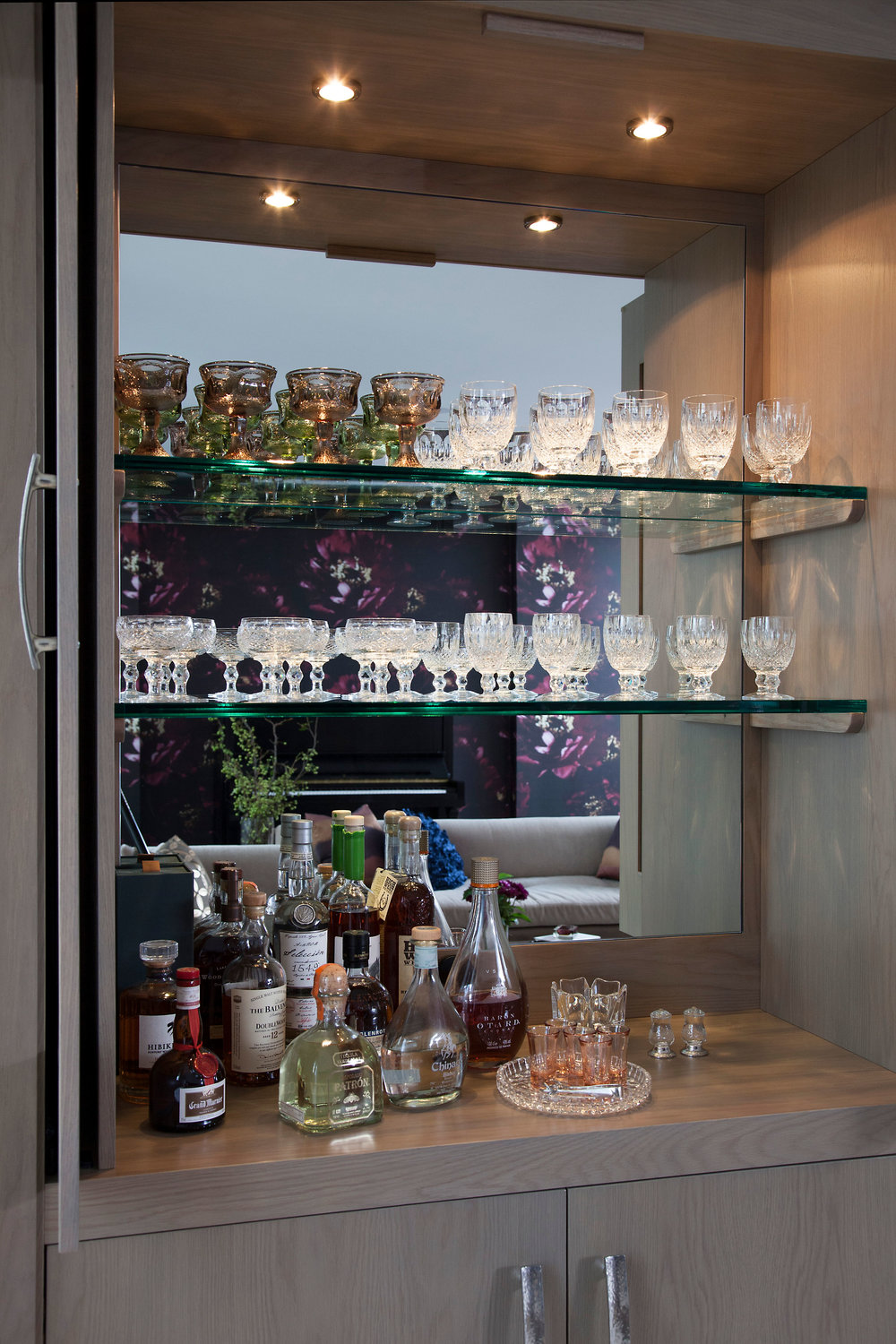 Precious Heirlooms and favorite drinks sparkle against these glass shelves. Hammered metal pulls add the finishing touch .