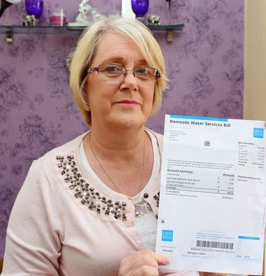 Angela Murtagh holding up an Irish Water bill which was sent to her mother Mary O'Brien who died six years ago