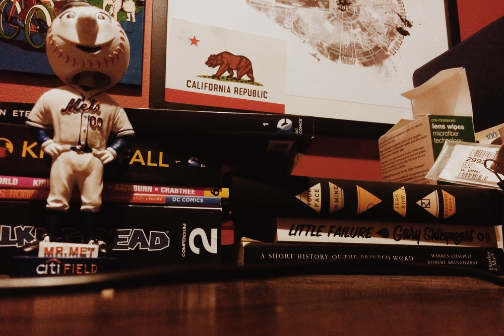 Mr. Met stands guard over my to-read piles -- graphic novels on the left, novels and non-fiction on the right.