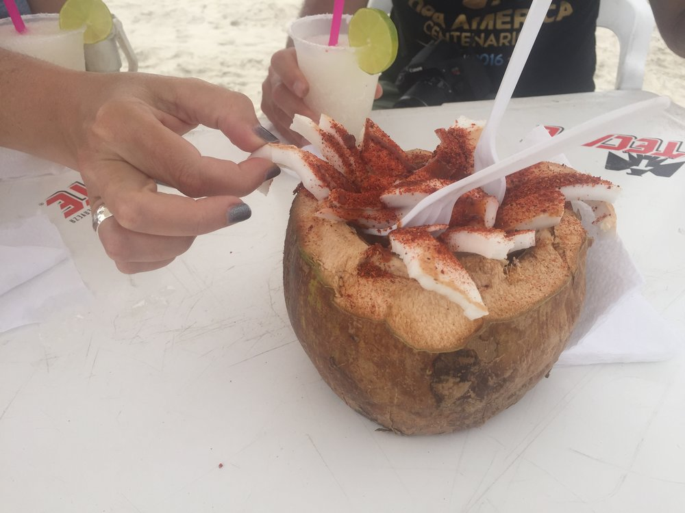 Our guests enjoying margaritas and snacking on spicy coconut slices on the Baja coast.