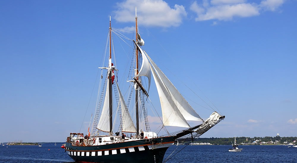 Flag –  Canada   Type of Ship –  Brigantine   Home Port –  Brockville, ON   LOA –  110 ft  Beam –   24.6 ft  Draft –  5.5 ft   History –   Fair Jeanne  began her life in the backyard of the Thomas G. Fuller, D.S.C.** M.I.D. R.C.N. She was designed and built by Capt. Fuller at his home in Britannia-on-the-Bay in Ottawa, Ontario. The keel was laid in 1978 and she was launched in 1980.  Fair Jeanne  was sailed by Capt. Fuller and his wife, Jeanne (now patron of Bytown Brigantine Inc.) in the Caribbean and to his old haunts in the European Seas. During the past 15 years, the ship has logged over 150,000 miles (240,000 km) in service.