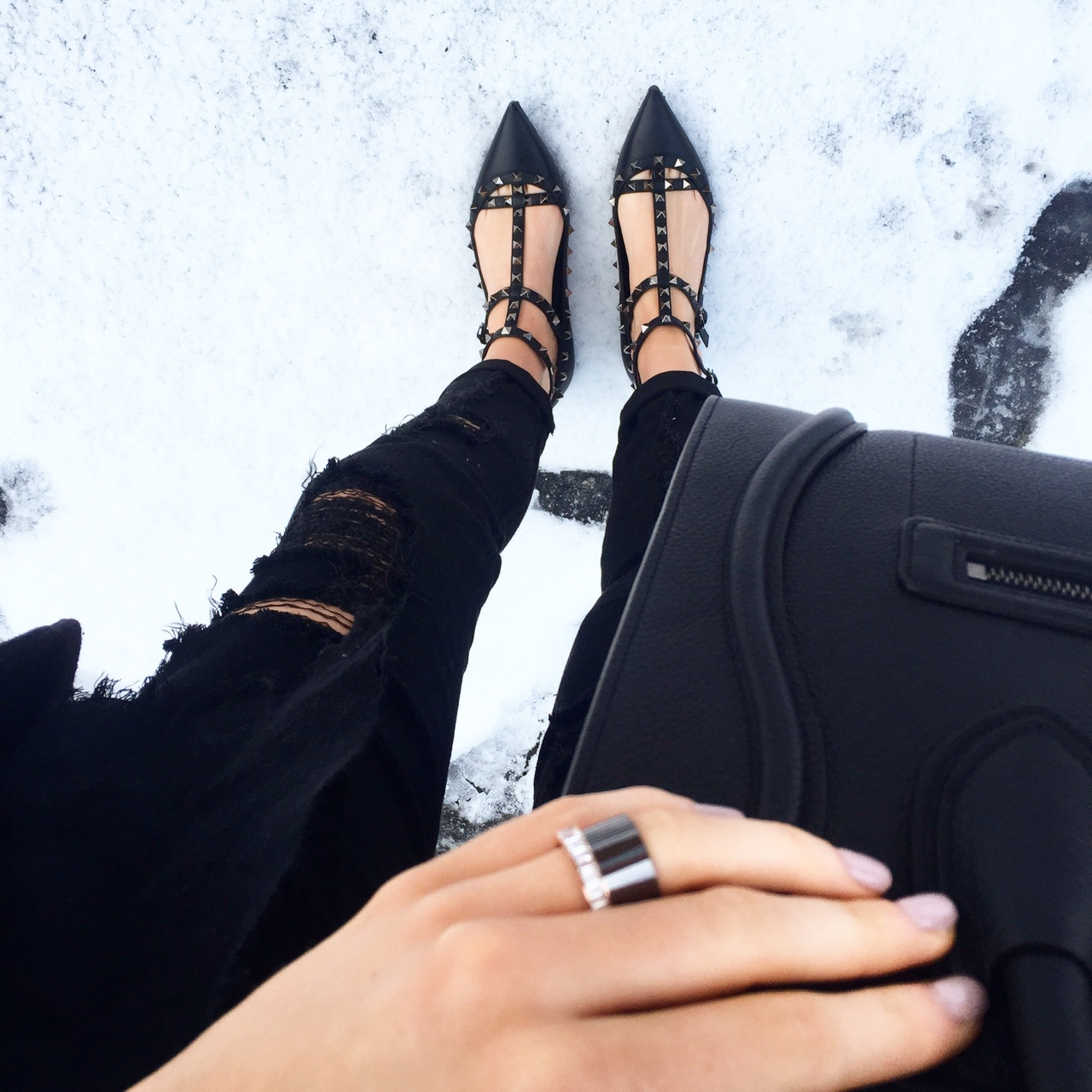 All Black Black ripped jeans with Valentino RockStud Cage Flats and Céline Luggage Tote in the snow. S H E