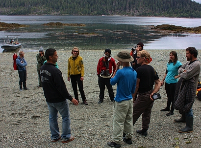 Watchman Sean Young (left, black jacket) greets ReEncounter group at Tanu; Master carver Jaalen Edenshaw at far right