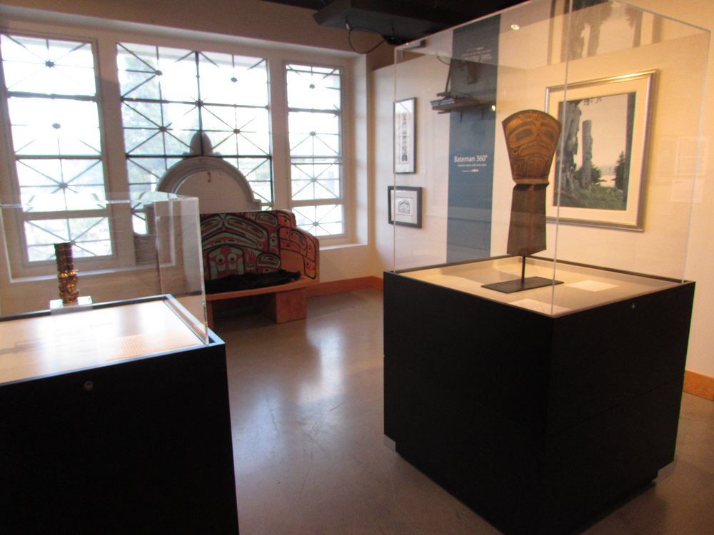 "Jim Hart's ""Three Watchmen"" maquette (left), bench by Jaalen Edenshaw & Guujaaw (back centre), Jaalen Edenshaw's ""The Wealth Bringer"" copper shield (right), and W. David Ward's ""Cast in Memory"" painting (back right)"