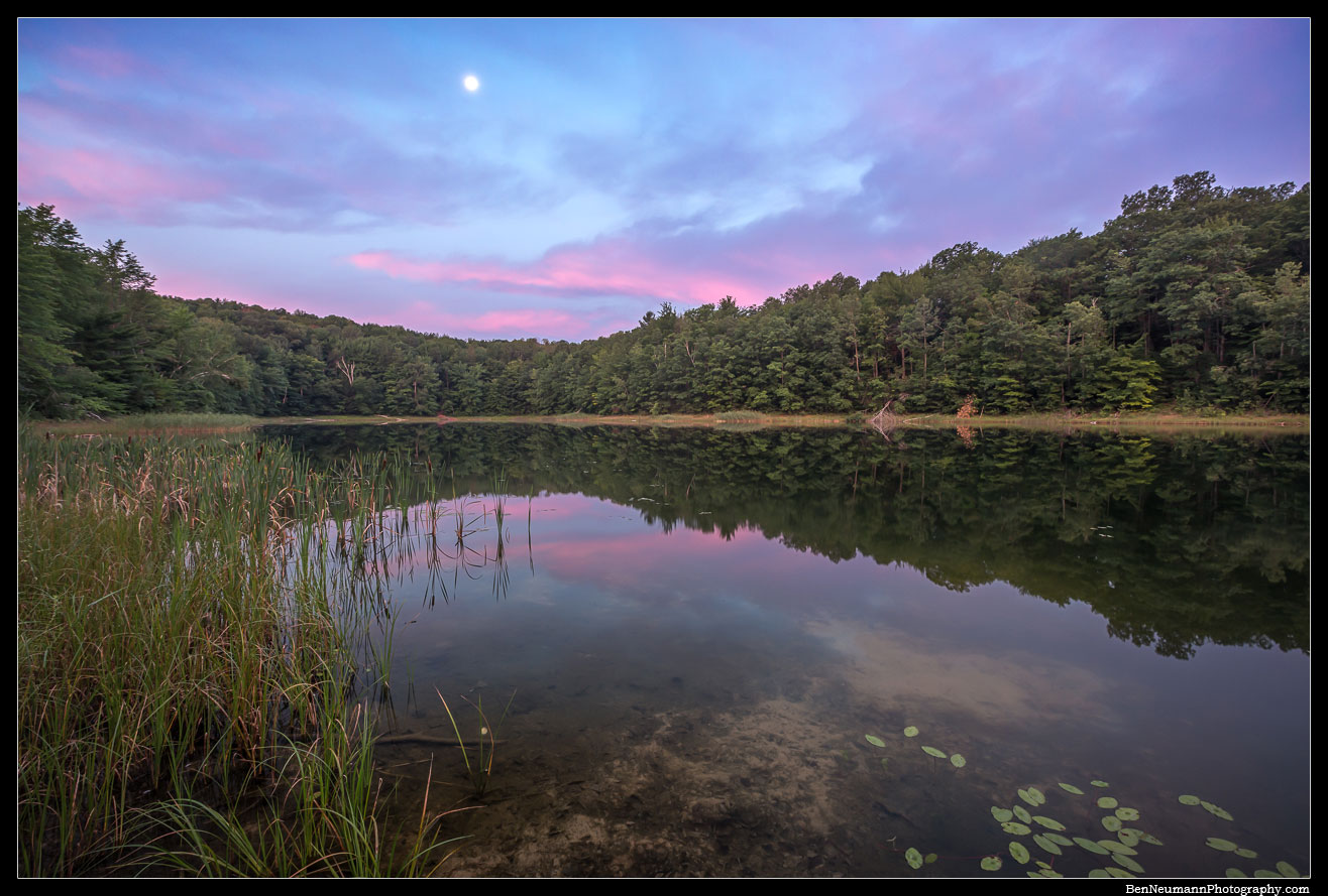 A secret lake in Leelanau County Michigan.I was out camping on a summers night when I woke and found the moon to still be out with the rising sun painting the clouds pink.
