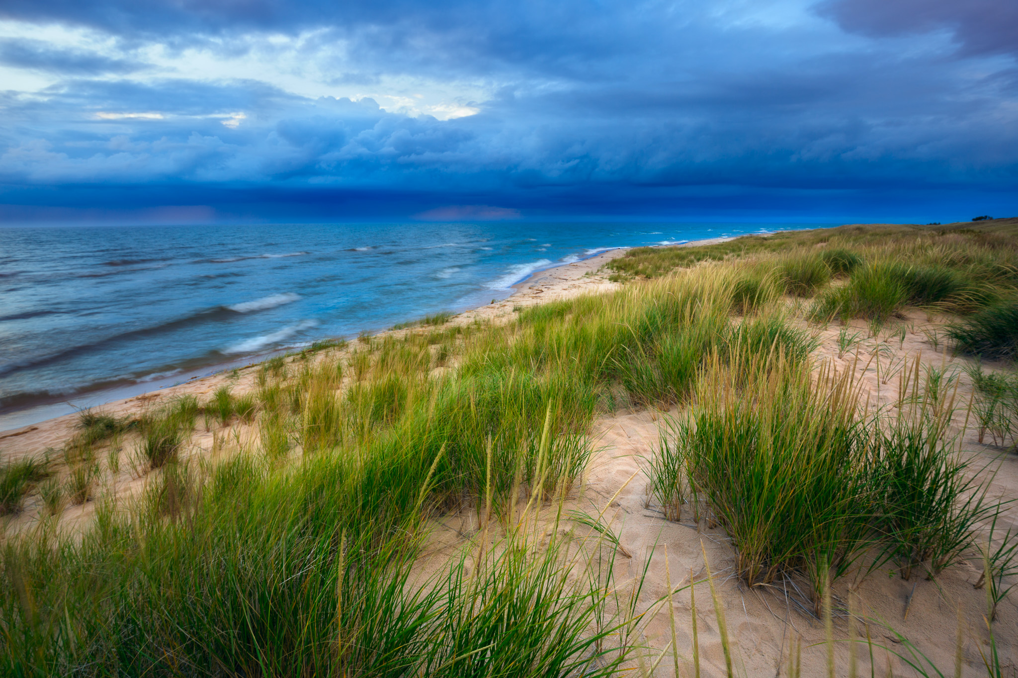 A very blue with a hint of purple storm moves across Lake Michigan of the shores of Ludington State Park.