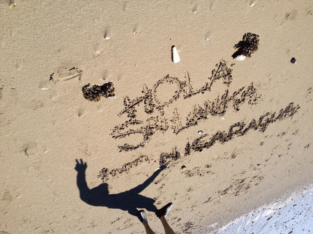 Anne writes a message to the citizens of Sri Lanka on a beach in Nicaragua on Sri Lanka's independence day (Feb 4).