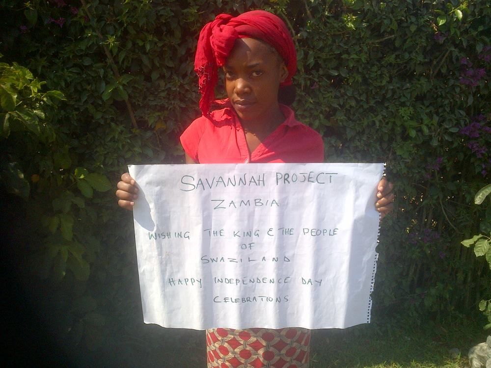 In Zambia, young men and women hold up letters they have written to the King and people of Swaziland.