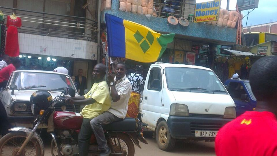Sessanga Denis and Kiwanuka Moses take a boda boda ride through the streets of Kampala, Uganda, waving the flag of St. Vincent and the Grenadines on the independence day of the islands (Oct 27).