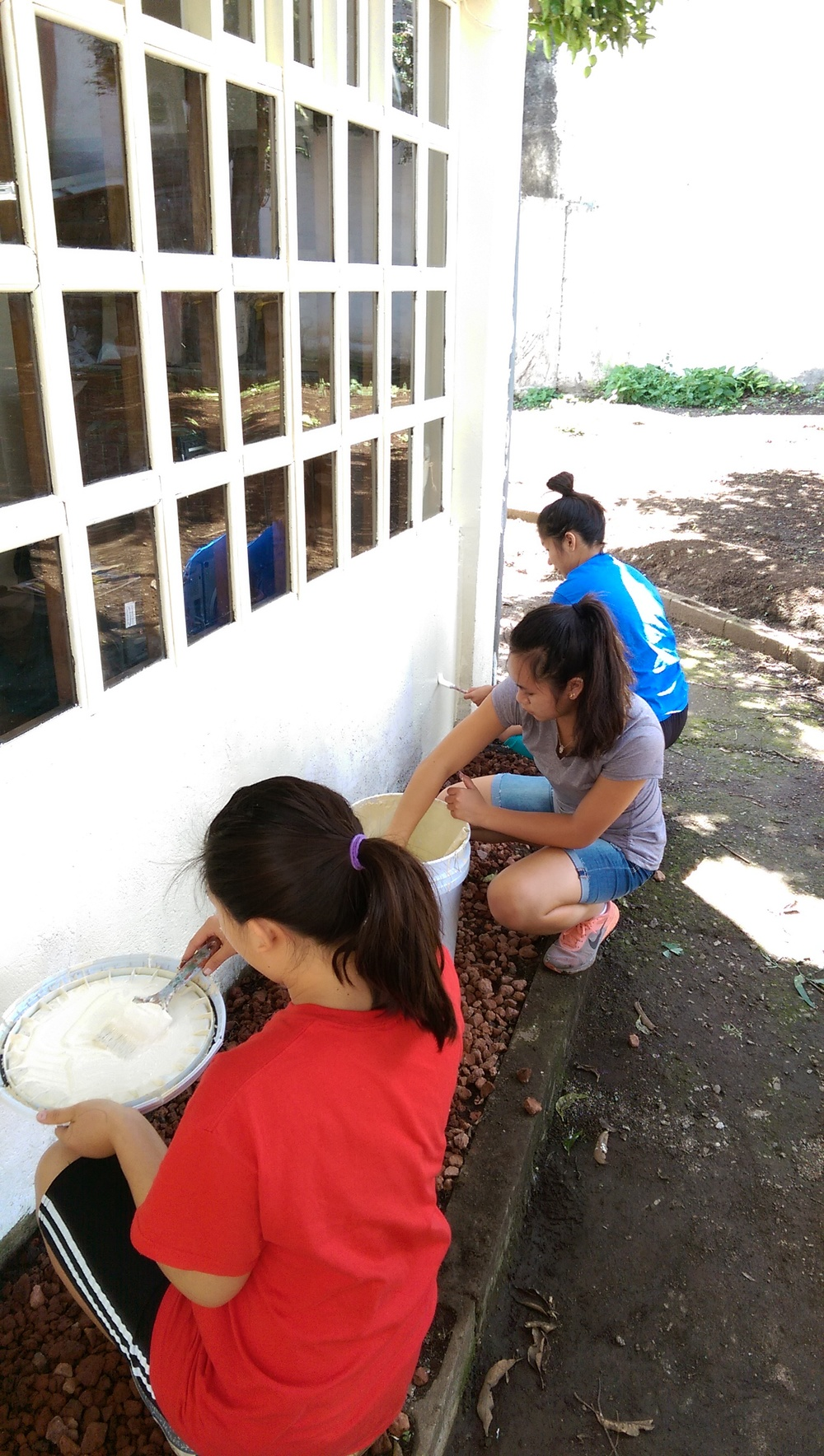 Danielle, Amy, and Lisa painting the wall of thehouse