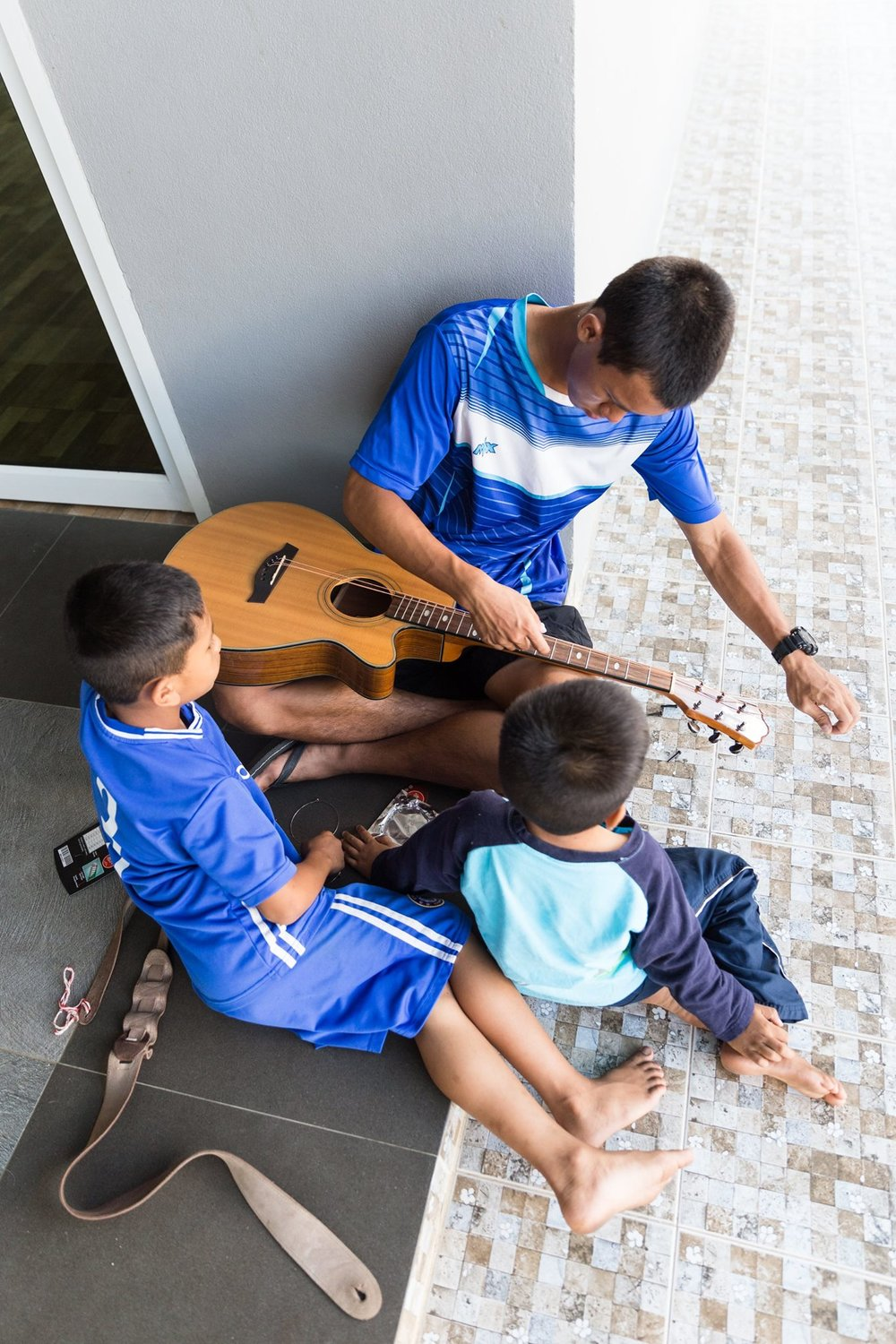 Younger kids watching Traipob work on the guitar