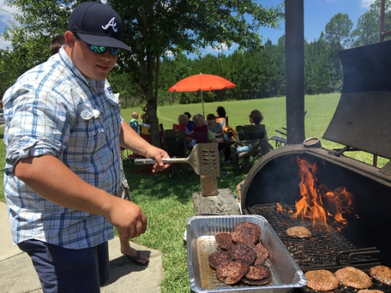 Grill Master Extraordinaire, Ben Ballowe showing those burgers who's boss.
