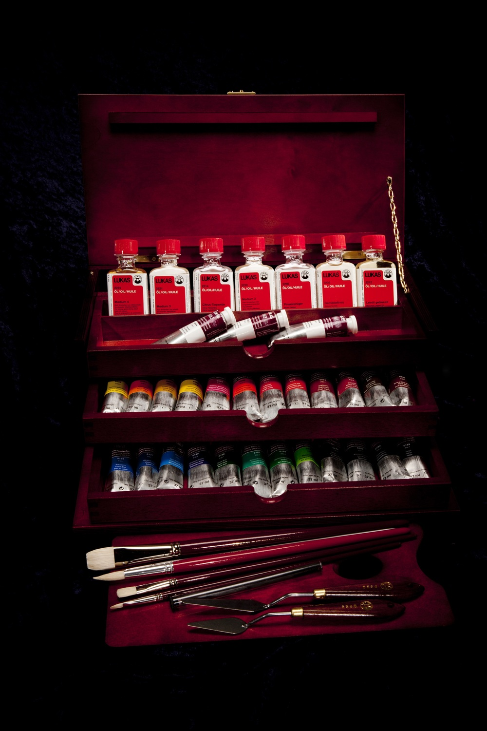 "This deluxe set is the perfect introduction to LUKAS 1862 Oil Colors! Now you can have the rich, 145 year history of LUKAS oils at your fingertips in this convenient ""treasure chest"" that also includes all necessary oil mediums and even brushes and sketching charcoal! This luxurious set of oil paints makes the ideal gift for both professional and amateur painters alike, or a beautiful way to keep your studio tidy and organized. Whether you're looking for a convenient, complete set up for a first-time oil painter, a way to broaden your painting experience and material knowledge, or a beautiful, lavish gift sure to be appreciated by any fine oil artist, this deluxe set of LUKAS 1862 Oil Colors and Mediums may just be what you're after! Deluxe set includes: Mahogany finished 3-drawer ""treasure chest"" 27 LUKAS 1862 Oil Colors in 37ml tubes 7 mediums in 50ml glass bottles 5 LUKAS brushes 2 wood-handled steel palette knives 2 pieces of sketching charcoal 1 wooden palette"