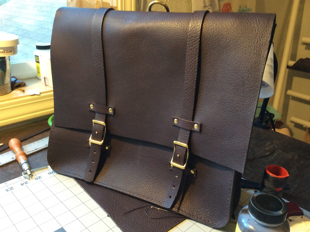 Leather messenger bag on the workbench.