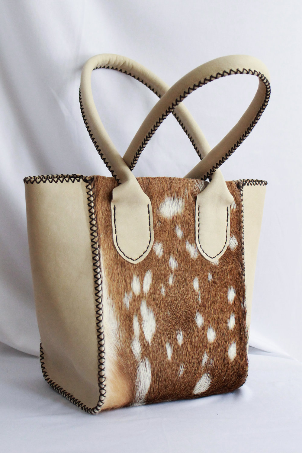 This amazing purse utilizes a vertical shape to get the most impact out of a great portion of Axis hair leather.