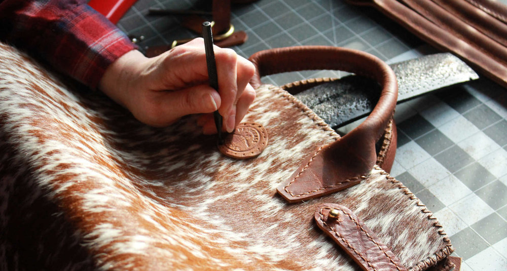 Here is Sam, hand-crafting this amazing hair-on-hide handbag right here in Montana!
