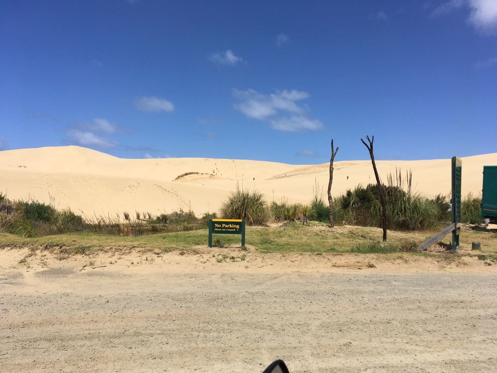 """Tässä paikallinen hiihtokeskus jonka näkeminen antoi vastauksen siihen,miksi maantien varteen oli perustettu sand board -vuokraamoja. """"Vuokraa hyvä lauta, tulihan shortsit ja aurinkorasva mukaan?"""""""