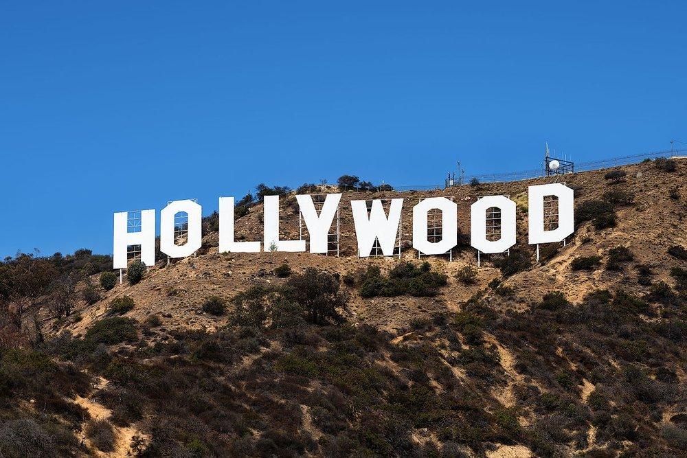 """Hollywoodin kasvaessa ja elokuvien suosion noustessa Hollywood-kukkulalle pystytettiin vuonna 1923 kyltti, jossa luki """"Hollywoodland"""". Kyltillä mainostettiin uutta kiinteistö-yhtiötä, eikä se siis alkuun liittynyt ollenkaan elokuviin. Kyltti oli valaistu 4 000 lampulla ja lampunkorjaaja asui pienessä talossa erään kirjaimen takana. Alun perin kirjaimet olivat hieman yli yhdeksän metriä leveät ja yli 15 metriä korkeat. Vuonna 1932 näyttelijä Peg Entwistle teki itsemurhan hyppäämällä H-kirjaimen huipulta alas, ja usein hänet muistetaankin juuri itsemurhansa eikä näyttelijäntaitojensa takia. Nykyisen muodon ja koon kyltti on saanut restauroinnin yhteydessä 70-luvulla."""