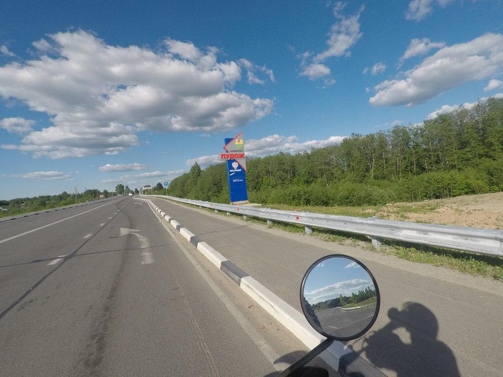 Tervetuloa Pudozhiin kyltti. Kansainvälisen matkailutien, Sinisen tien, päätepiste on muuten Puudozhin kylä. Sininen tie johtaa Norjan Mo i Ranasta Ruotsin ja Suomen halki Karjalan tasavaltaan.