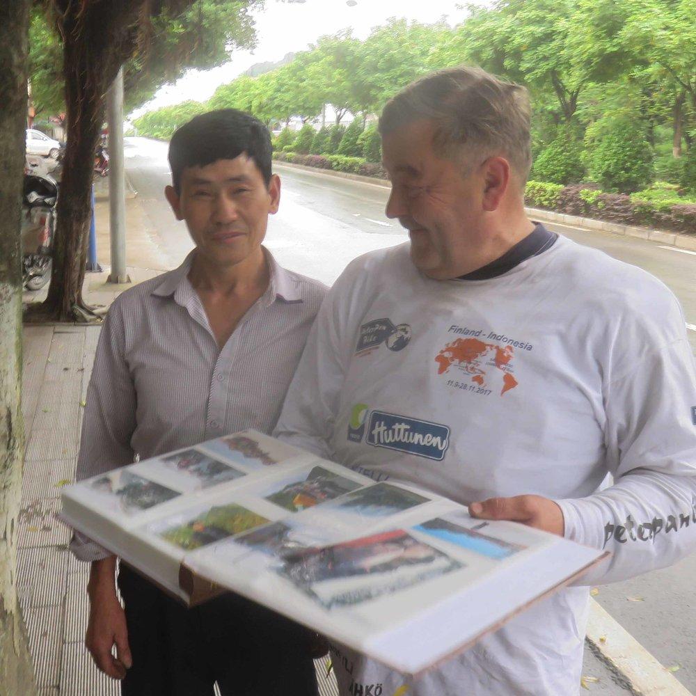 Jussi katsomassa Mr Wongin kuvia... joka myös motoristi... ja jonka liikkeen eteen pysähdyimme sattumalta!