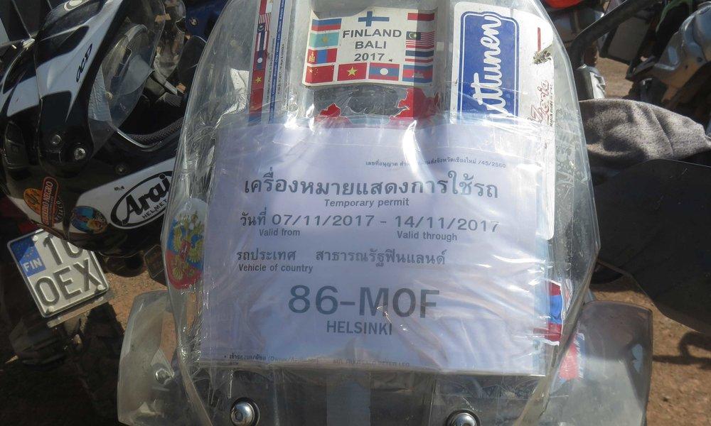 Temporary permit jolla saamme ajaa Thaimaassa 14.11.2017 saakka. Alla paikallisoppaamme Mr George teipaamassa permittejä pyöriin!