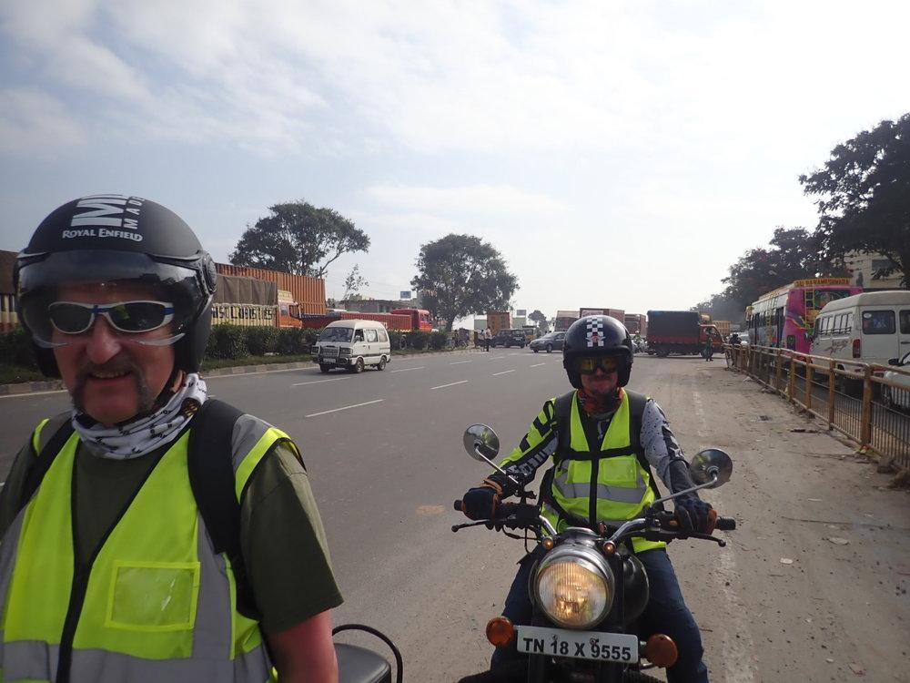 Hosurista noin 10km etelämpänä on Tamil Nadun ja Karnatakan raja. Mopot pääsevät livahtamaan koloista ja ojan kautta, mutta rekat ja henkilöautot tarkistetaan. Sitä ruuhkan määrää on vaikeaa suomen kansalaisen kuvitella! Hoituisi ehkä vähän nätimmin rajamuodollisuudet pienellä organisoinnilla, mutta kun ei - kaikki tunkee väleistä ja ohittelee miten sattuu!  Tässä kuvassa Mikko ja Kai ovat jo pahimman tukoksen ohi päässeet - odotellaan muita...
