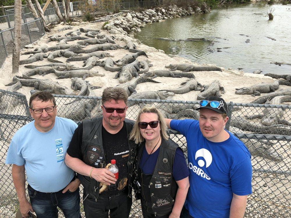 Harry, Kaitsu, Ilse ja Jalmari perhepotretissa odottelemassa alligaattoreiden ruokinta-aikaa. Epäiltiin josko ruokinta tarkoittaa noiden turva-aitojen kaatamista...